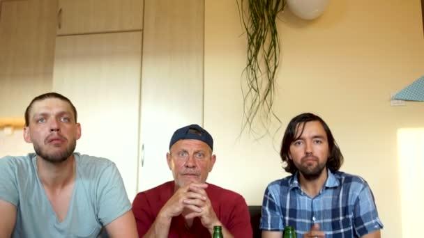 Zwei Generationen von Männern, drei Fußballfans, die zu Hause vor dem Fernseher nach ihrer Lieblingsfußballmannschaft wühlen. Männer trinken Bier und brüllen ein Tor