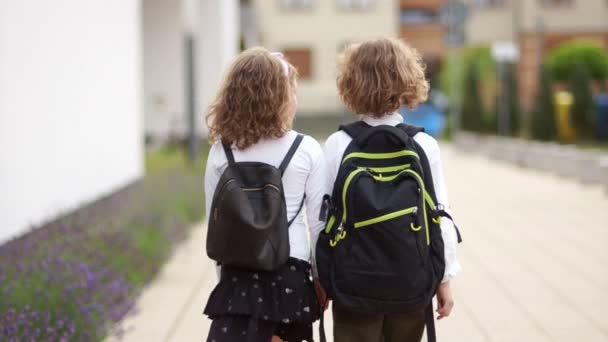 Két göndör iskolások, egy fiú és egy lány, hátizsák iskolába menni. Vissza a véleményt. Vissza az iskolába tudás nap