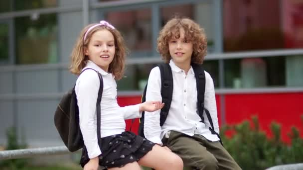 Two curly schoolchildren, school friends, foolishly sitting on the railing near the school. Children are dressed in school uniform, backpacks. Back to school.