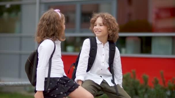 Chlapec a dívka se mluví v blízkosti školy. Dívka byla v rozpacích, usmála se a odvrátil. Školní láska, první láska