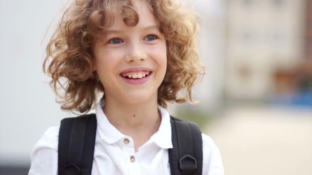 süße und glückliche lockige blauäugige Junge, der lacht und in die Kamera schaut. Der Schuljunge trägt ein weißes Hemd und einen Schulranzen. Schulferien, zurück in die Schule, glücklicher Schuljunge