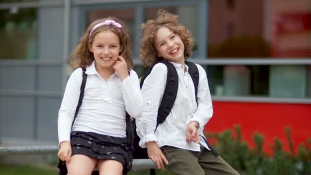The boy and the girl are fooled after finishing school at school. First day at school, fooling around, happy schoolchildren
