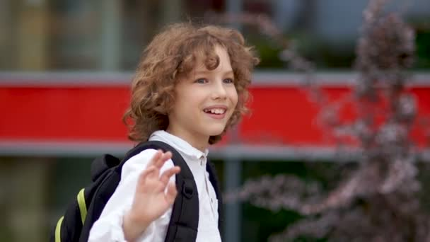 A close up portrait of a curly blue-eyed schoolboy. The boy waves his hand and laughs. happy schoolboy, back to school