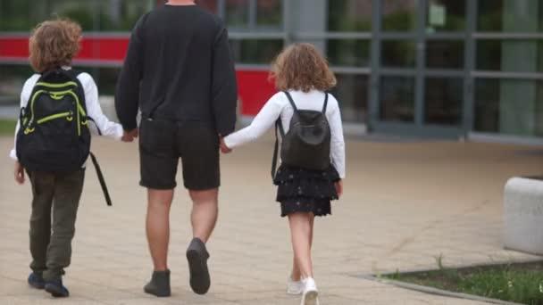 Otec vede své děti do školy. Muž drží chlapce a dívku do náruče. Jdou do školy s batohy. Zpátky do školy, šťastná rodina
