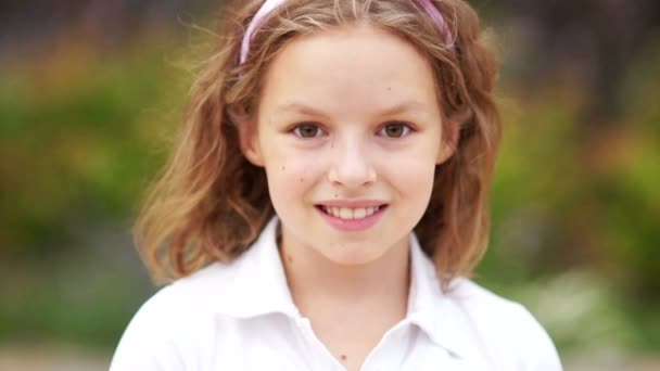 Close up of a little blonde brown-eyed cute girl face. Girl blinking her eyes and smiling. Inside. Portrait shot. Happy schoolgirl