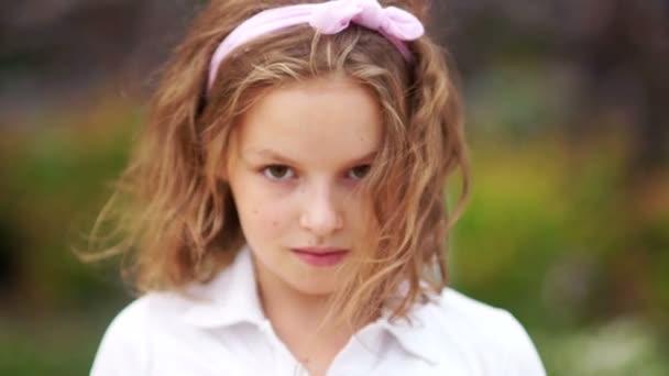 Szép göndör barna szemű iskolás nézi a kamerát. A szél zörget a haját. Közel álló, lassú mozgás