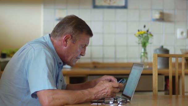 ein Mann im Rentenalter benutzt einen Laptop und ein Telefon. er schaut sorgfältig auf den Computerbildschirm, schielt, zieht Brille an, Kurzsichtigkeit