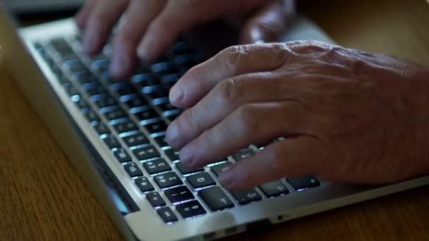 Internet-Technologien für Menschen im Rentenalter. Close-up Portrait von älteren mans Hand Texteingabe auf Laptop-Tastatur