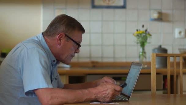 Internet-Technologie für Rentner. Ein älterer Herr arbeitet mit seinem Laptop, während er am Küchentisch sitzt. er hebt seine Brille und lehnt sich zum Bildschirm, der besser aussehen sollte