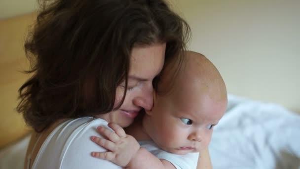 junge Mutter hält ihr Baby im Schlafzimmer. Eine Frau umarmt vorsichtig ein drei Monate altes Baby. Muttertag