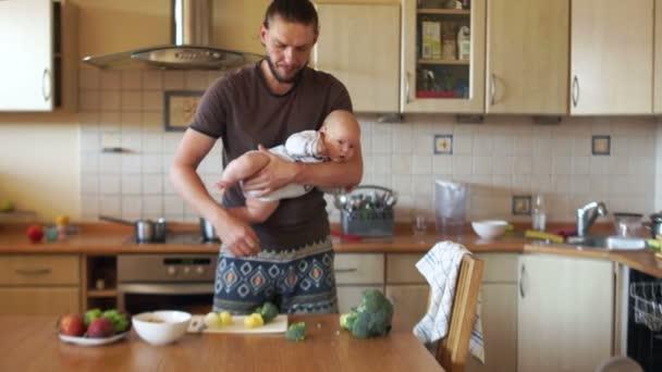 Egy fiatal modern apa főz ételt a konyhából, egy három hónapos baba tartja a karjában. Egyedülálló szülő, apák napja. Egy ember van egy elegáns szakáll és egy lófarokba a háton és a fej
