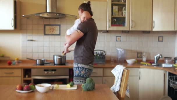 Father and baby in the kitchen. Fathers day, day without mom. Care of babies. A young man prepares a meal, holding an infant in his arms, stirs the soup with a ladle. Fathers Day