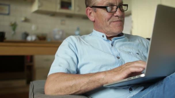 Ein älterer Mann sitzt in der Küche und arbeitet am Laptop. er entspannt sich und lächelt leise. ein Mann mit blauem Sommerhemd und Brille.