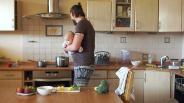Man in the kitchen holding a child on his shoulder, cooking in the pan. New born, bonding concept, happy family, Fathers Day