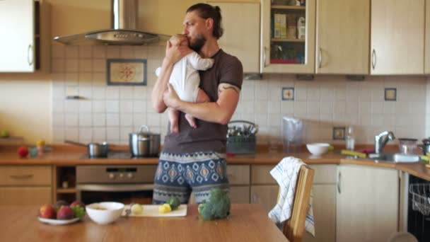 An attractive father cooks soup in the kitchen holding his little son in his arms. Dad on maternity leave