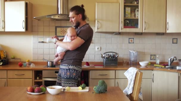 A successful young father feeds the baby in the kitchen. Baby care, bottle feeding. Fathers Day