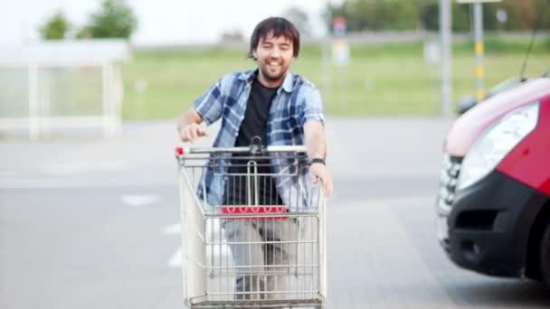 Veselý mladík se bavit na parkoviště nákupního centra. Happy zábavný chlap jezdí na nákupní košík. Zákazník s nákupním vozíkem supermarketu