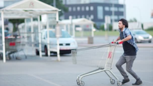 Man have fun on the parking shopping mall. Happy funny guy rides on shopping cart. Customer with shopping trolley near supermarket