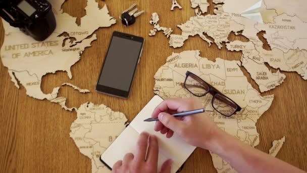 Mapa světa z dřeva. Muž píše plán své cesty v poznámkovém bloku. Příprava pro cestování. Cestovní kancelář