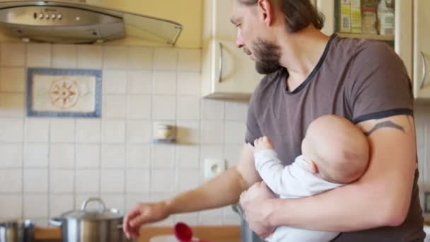 A busy father. A man with a child in the kitchen prepares lunch and feeds the baby from the bottle. Fathers Day