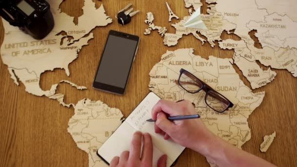 The man is planning a tourist trip to Morocco. Wooden map of the world map on the table, paper airplane on the map, notebook, list of countries
