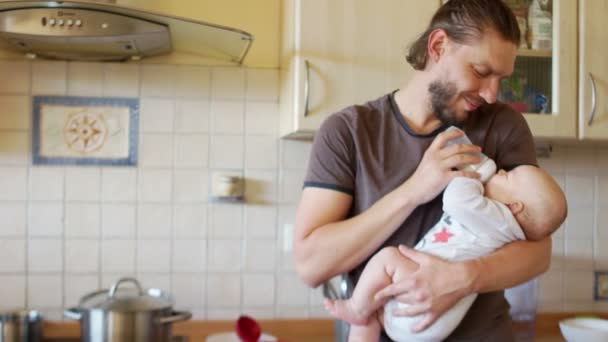 The baby eagerly drinks milk from the nipple in the hands of his father. The baby sneezes, the man smiles. Fathers day, fathers care