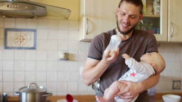The guy feeds the baby from the nipple, kisses him on the forehead. He lifts him in his arms, puts it in a column, belches. The kid smiles and turns his head. Care for babies up to a year.