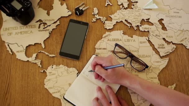 A man writes in his notebook the plan for his travels. Germany, Spain, Egypt, Turkey - and rearranges the paper airplane on the world map. Travel agency, tour organization