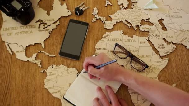 ztratit up muž píše ve svém zápisníku plán své cesty. Cestovní kanceláře, tour organizace. Dovolená, letní dovolená