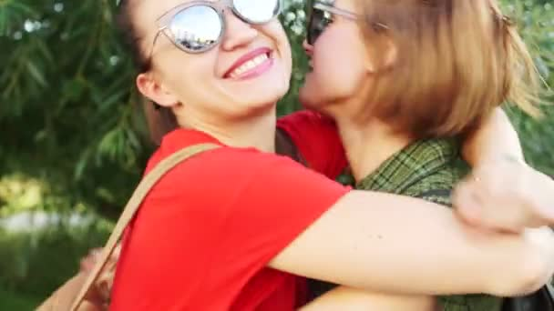 Dynamic video. Lovely girl in sunglasses for a walk in the park. A couple of girlfriends laugh and hug. Red lipstick