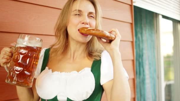 junges sexy Oktoberfestmädchen - Kellnerin, in traditioneller bayerischer Tracht, serviert große Bierkrüge und isst Brezel auf Holzuntergrund