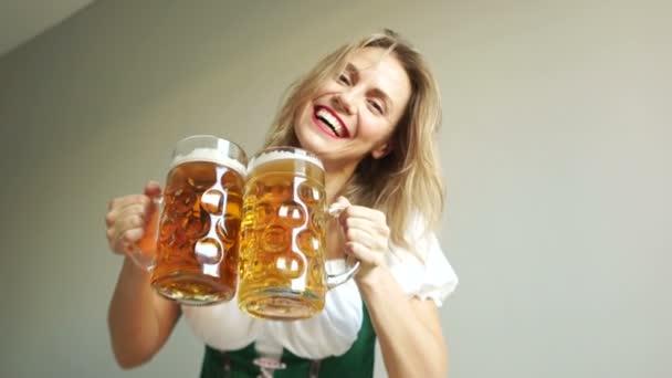 eine schöne blonde Frau mit zwei großen Gläsern Bier in bayerischer Tracht. Gläser klirren, lachen und jubeln. Bierfest