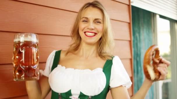 junge sexy Oktoberfestkellnerin in bayerischer Tracht, die große Bierkrüge serviert
