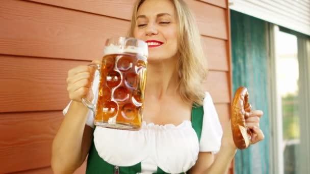 reife sexy Oktoberfestkellnerin, in bayerischer Tracht, serviert große Bierkrüge