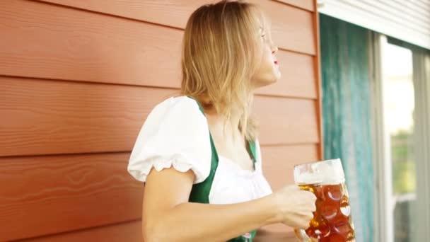Ein Model in bayerischer Tracht mit einem Glas Bier und einer Brezel in der Hand ist wütend und flucht. roter Lippenstift