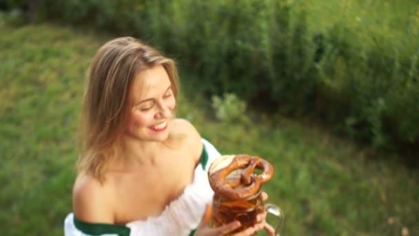 junges sexy Mädchen in bayerischer Tracht kauft Bier und Brezel auf dem Oktoberfest. , lacht eine Frau fröhlich und kauft gern. auf grünem Hintergrund