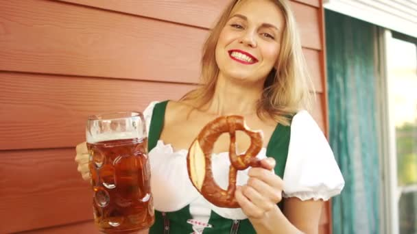Mädchen mit Bier und Brezel, Barmann beim Oktoberfest. sexy weißzahniges Lächeln, rote Lippen, aufrichtige Freude. Bayerische Tracht