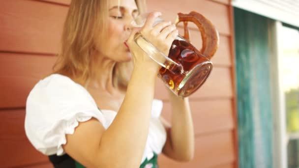 Frau trinkt eifrig Bier aus einem großen Glas. auf dem Oktoberfest, deutsche nationale Traditionen. Fokus auf die Hand mit einem Glas