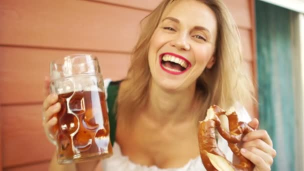 Close up portrait of an oktoberfest girl in a traditional national Bavarian costume with a glass of beer and kredelem in her hands. A woman with pleasure drinks beer from a misted glass
