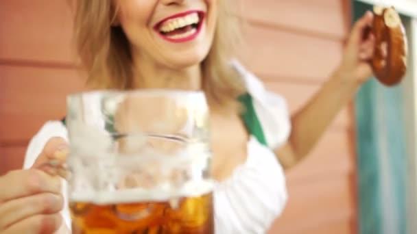 Gläser mit Bier klirren lassen. ein Mädchen auf dem Oktoberfest. Tracht aus Bayern, Nahaufnahme