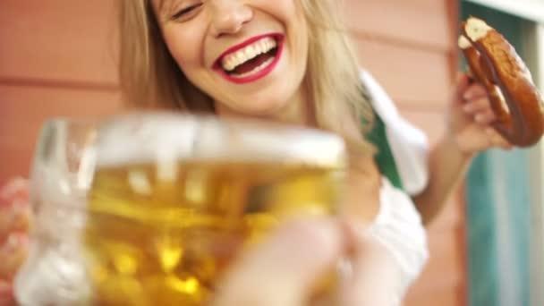 Im Alkoholrausch trinkt ein junges Mädchen auf dem Oktoberfest Bier, sie ist sehr fröhlich und lacht laut. in bayerischer Tracht