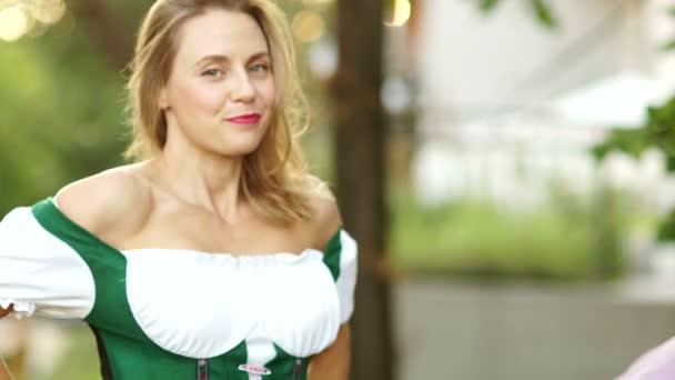 Blonde fröhliche Bayerin im Dirndl. Das Mädchen lächelt, blickt in die Kamera, flirtet, zeigt das Dekolleté, rote Lippen. Oktoberfest, Bierfest, Kopierraum