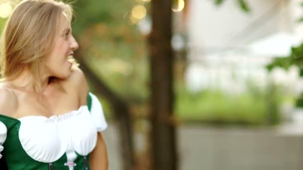 Dívka v bavorském kroji bere sklenici piva od barman na pivní festival Oktoberfest. Žena je šťastná a smích, je překvapen a veselá. Na čerstvém vzduchu