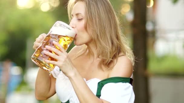 Oktoberfest Bierfest. Ein Mädchen im traditionellen bayerischen Anzug trinkt Bier und wischt sich peinlich berührt den Schaum über die Lippen. rote lippen, sexy, erotisch
