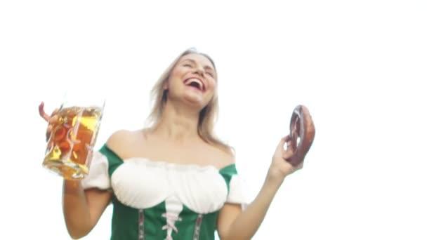 Ein wunderschönes tanzendes Mädchen in Oktoberfesttracht hält einen Bierkrug und eine traditionelle bayerische Brezel in der Hand. beugt sich die Frau über die Kamera, die Ansicht von unten. Tanz zum Oktoberfest