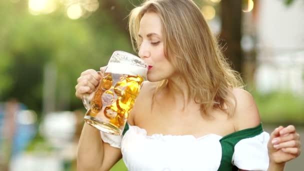 Musikalisches Oktoberfest. Die reife Frau im traditionellen bayerischen Anzug trinkt Bier und wischt sich peinlich berührt den Schaum auf die Lippen. rote lippen, sexy, erotisch