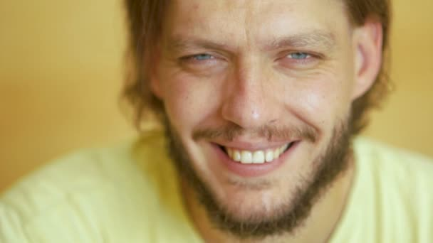 A blue-eyed young man with a beard looks at the camera and cheerfully smiles. A beautiful white tooth smile. Optimism, positive attitude, good mood