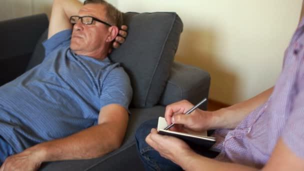 Zralý muž je ležet na gauči a mluví k psychiatrovi. Psychologickou pomoc, duševní zdraví, problémy seniorů