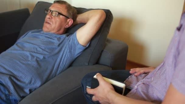 Muž v recepci psychiatři. Doktor si klade otázky k pacientovi. Muž leží na gauči, psycholog nenapíše