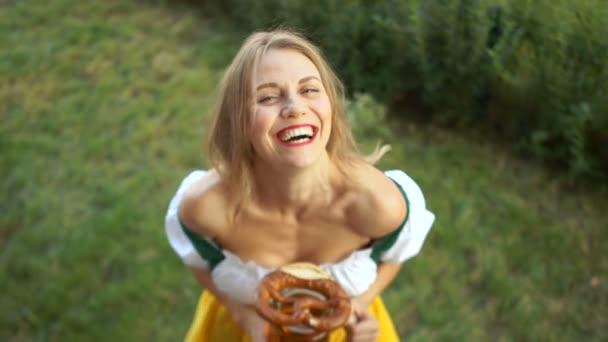 Oktoberfest. Eine Frau im bayerischen Anzug mit einem großen Glas Bier und einer Brezel in der Hand lacht fröhlich und blickt in die Kamera. Ansicht von oben